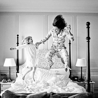 mum and daughter jumping on the bed in a hotel room black and white picture
