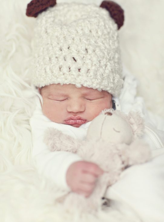 newborn baby wearing cream outfit and hat lying on cream fluffy blanket holding a teddy bear